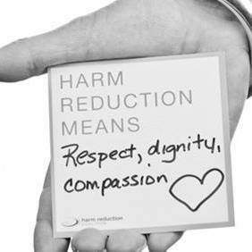 hand holding card that says harm reduction means compassion
