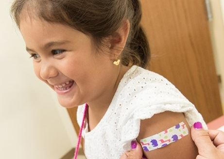 girl smiling getting a bandaid on arm