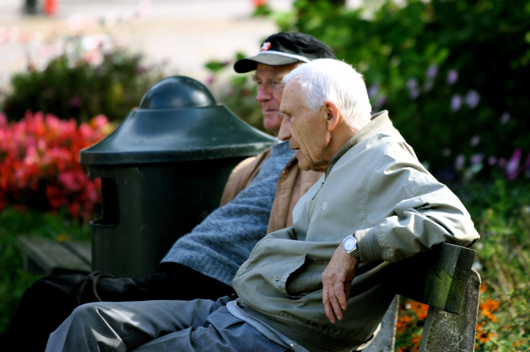 two senior men sitting on a bench outside