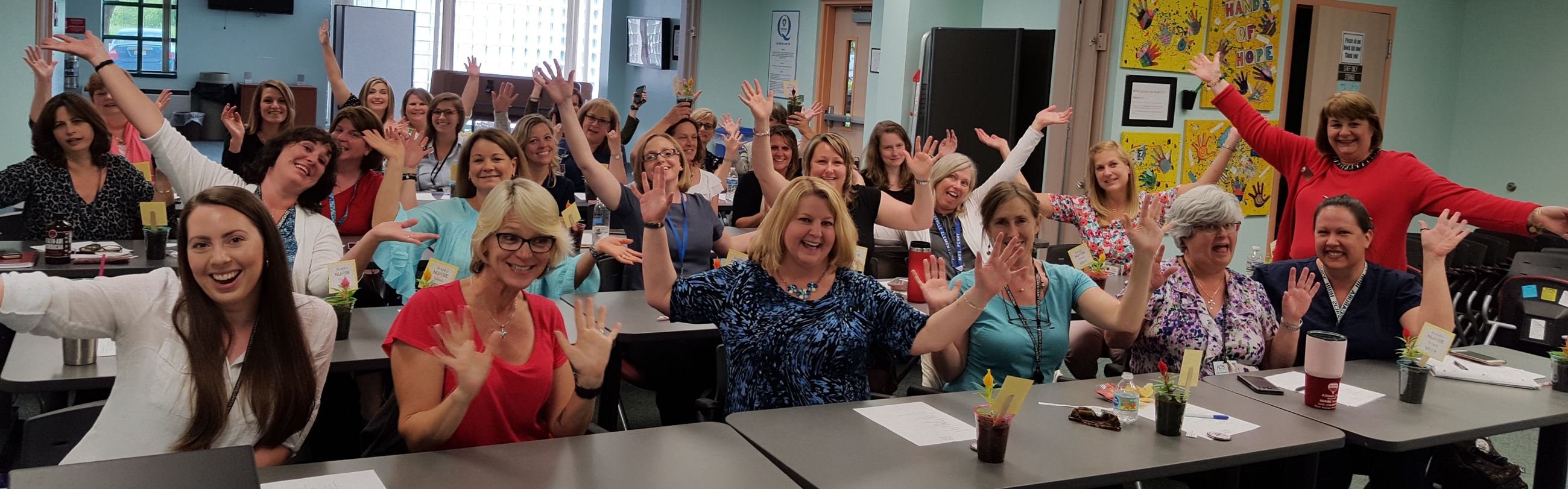 group of school nurses smiling with hands in the air
