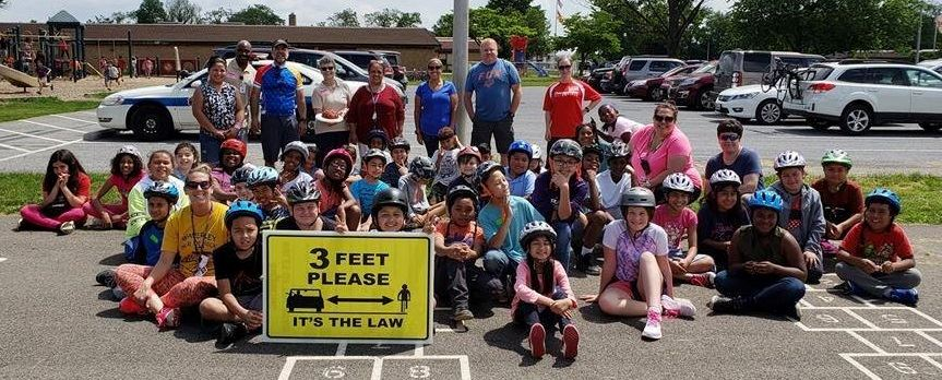 Group of fourth graders wearing bike helmets, smiling, with adults in background
