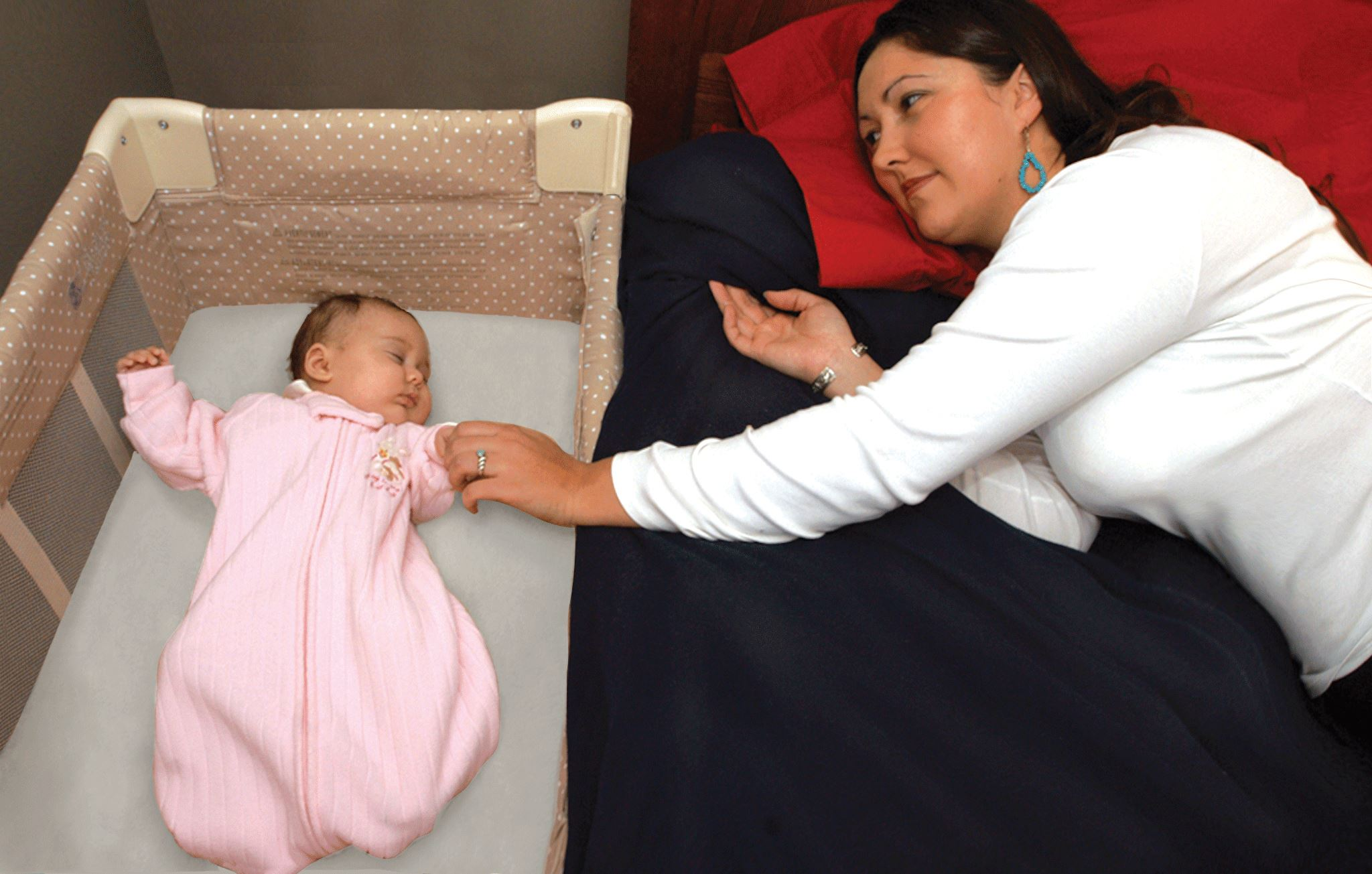Woman sleeping in bed next to baby's crib. Baby sleeps in own crib.